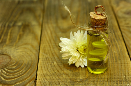 bath essence: Natural organic flowers oil in handmade bottle and flower are on the wooden table with place for text