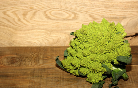 Romanesco broccoli, or Roman cauliflower on wooden background in rustic style. Space for text. Banco de Imagens