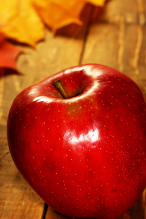 caes: Close up ripe natural organic apple on fall autumn leaves on wooden background with copyspace for you text.