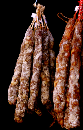 Smoked ham meat natural farm jerked smoked sausage pork in a traditional way hanging on dark background Stock Photo