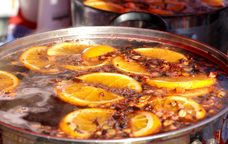Mulled wine, punch, sangria, with cinnamon, orange, spices and citrus fruit. Hot warming drink cooked in a pan outdoors. Close up.