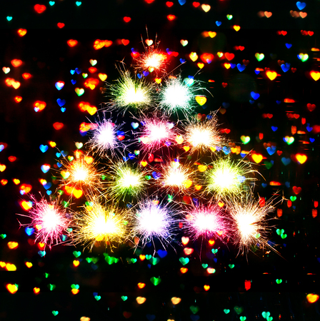 Christmas New Years tree form fireworks sparks on hearts dark background