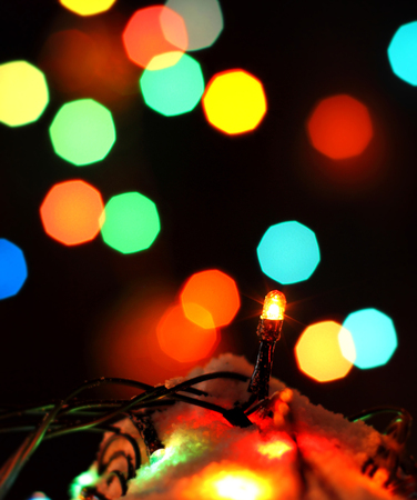 celebrat: Merry Christmas, Happy New Years garland colorful lights in night snow with bokeh dark colorful background. Conceptual image for celebration greeting card copyspace, place for text