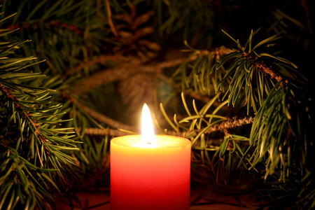 Beautiful Christmas candle with New Yera`s tree brunch on dark background Reklamní fotografie