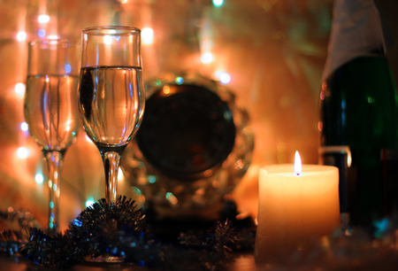 party streamers: Style New Years Eve celebration background with horse an elegant arrangement with a clock counting down to midnight, flutes and bottle of champagne and party streamers with a candles.