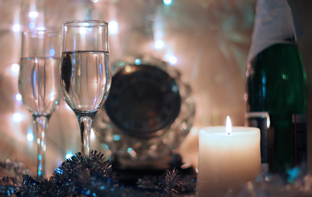 flutes: Style New Years Eve celebration background with horse an elegant arrangement with a clock counting down to midnight, flutes and bottle of champagne and party streamers with a candles.