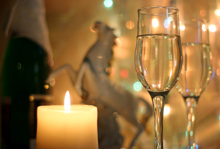 party streamers: Light style New Years Eve celebration background with horse an elegant arrangement with a clock counting down to midnight, flutes and bottle of champagne and party streamers with a candles.