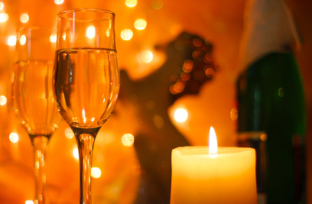 champagne celebration: Style New Years Eve celebration background with horse an elegant arrangement with a clock counting down to midnight, flutes and bottle of champagne and party streamers with a candles.