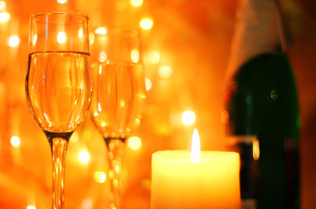Bright yellow Christmas greetings card or New Years Eve celebration background with an elegant arrangement with flutes and bottle of champagne and burning candles. Bokeh light garland backdrops.