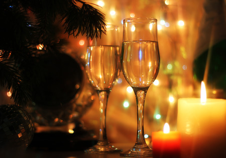 flutes: New Years and Christmas Eve celebration background with an elegant arrangement with a clock counting down to midnight, flutes and bottle of champagne and party streamers with a candles.