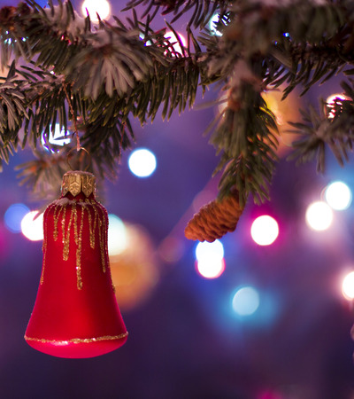 Christmas and New Year`s bokeh image. Red bell toy decorations on tree, fir cones and tree branches. Greeting card Background concept with holiday tinsel with copyspace place for text.