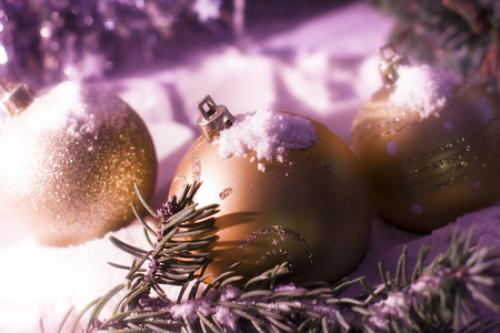 Christmas and New Year`s. Toy gold balls on tree, fir cones and tree branches covered with snow. Greeting card Snowy Background concept with holiday tinsel. Stock Photo