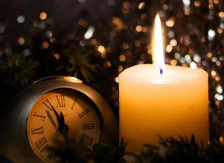 watch new year: Christmas and New Year`s vintage clock showing five to midnight. Festive evening burning candle and fir tree branches covered with snow. Background with holiday tinsel, copyspace for text. Stock Photo