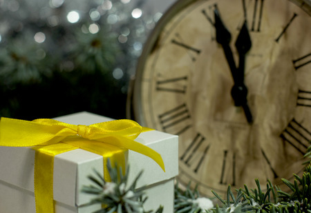 Christmas and New Year`s vintage clock showing five to midnight. Festive evening with gift box, Christmas tree fir branches covered with snow. Concept for congratulations and party.