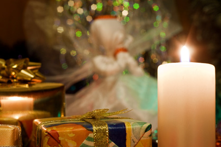 praying angel: Christmas and New Year`s evening burning candle and many present gift boxes with bows of gold ribbons. Praying angel hand made craft decorations. Retro style greeting card background with tinsel. Stock Photo