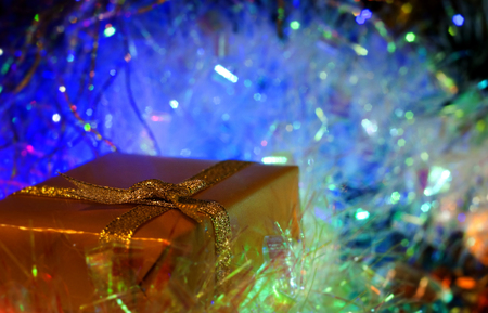 illustrati: Christmas and New Year`s colorful blue glow light and gift boxes gold wrapping paper with bows of ribbons. Greeting card blue Background with holiday tinsel.