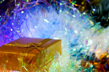 illustrati: Christmas and New Year`s colorful blue glow light and present boxes gold wrapping paper with bows of ribbons. Greeting card blue Background with holiday tinsel. Stock Photo