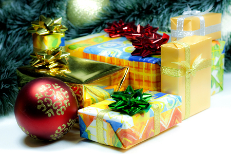 illustrati: Christmas and New Year`s many gift boxes wrapped in colorful and gold wrapping paper with bows of ribbons. Retro big toy red glass ball, fir tree branches isolated on white background. Stock Photo