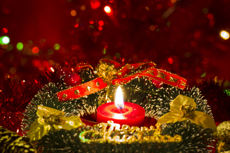 pine wreaths: Green Christmas wreath with decorations and burning candle on red lights bokeh background Stock Photo