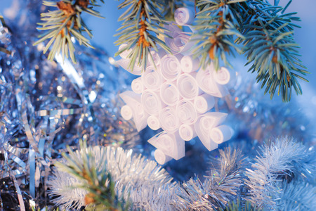 Handmade Christmas gifts toys quilling snowflake from paper vintage on fir tree branches and blue lights bokeh background.