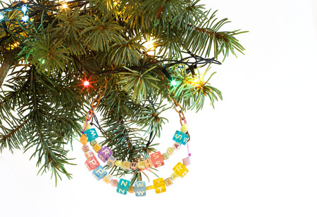 Happy New Year and merry Christmas card beaded letter garland on fir tree brunch and garland colorful lights isolated on white background. Copyspace place for your text. Frame corner.