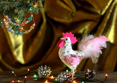 tissu or: Happy New Year 2017 of rooster card with hand made craft white rooster on old wood and beaded letter garland on Christmas tree branch on gold cloth background. Copyspace place for text.