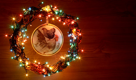 decoupage: Happy New Year 2017 on the Chinese calendar of rooster template copyspace card with hand made craft roosters decoupage in decorated Christmas wreath and garlands of colored light. Wooden background.