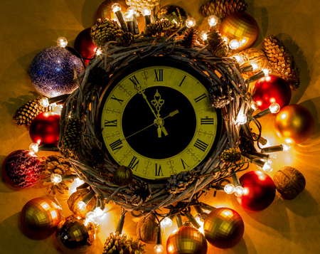 ew Year hand made Concept. Time Nearly Twelve Oclock Midnight. Christmas clock in wreath and garlands of colored light bulbs with craft decorations.