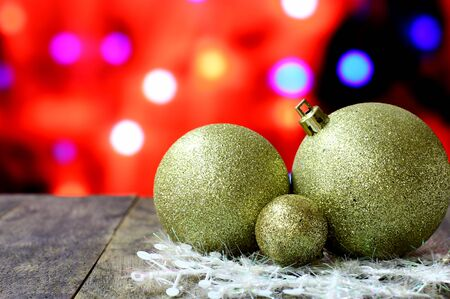 dcor: Christmas background with gold balls decorations on old dark wooden desk table. Colorful holiday bokeh garland lights. Wood foreground and ready for product montage.