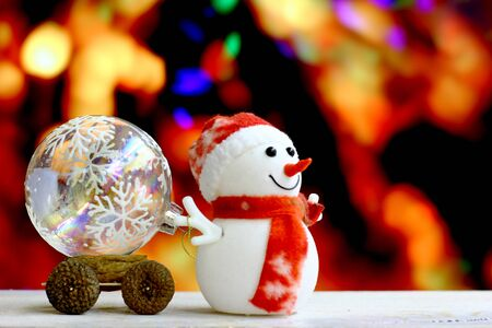 dcor: Christmas and New Year`s background with glass balls in child craft truck and snowman toys. Colorful holiday bokeh garland lights. Copyspace concept congratulations card.