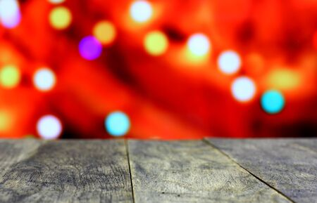 dcor: Christmas background with empty old dark wooden desk table. Red, orange, yellow holiday bokeh garland lights. Selective focus on wood foreground and ready for product montage.