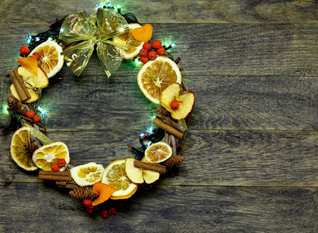 Christmas hand made craft on old wooden background. Traditional New Year`s door wreath components from dried oranges, cones. Stock Photo