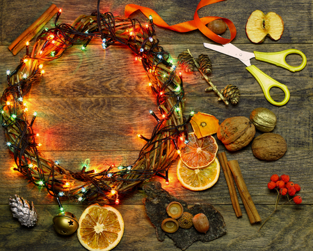 dcor: Christmas hand made craft template background. Make traditional New Year`s door wreath components: tree cones, dried oranges, cinnamon, ribbon and colorful garland lights. Copyspace for text. Stock Photo