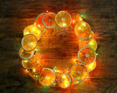 dcor: Christmas hand made craft template. Evening light wooden background. Traditional New Year`s door wreath components from dried oranges and colorful garland lights. Copyspace frame for logo and text.