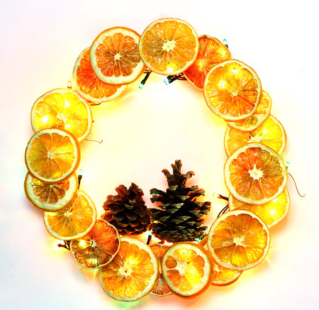 dcor: Christmas hand made craft template white background. Traditional New Year`s door wreath components from dried oranges, cones and colorful garland lights. White Copyspace frame for logo and text.