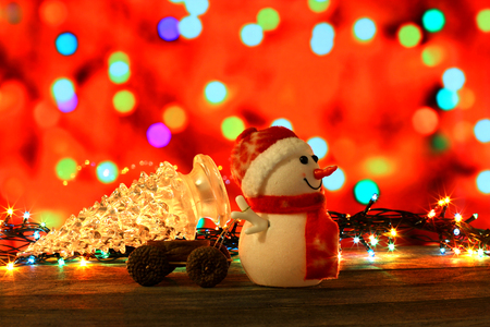 dcor: Dark evening Christmas and New Year`s card or poster with Snowman drags a truck bright glass tree on colorful bokeh background. Big copyspace place for text, logo, sale price and item description.