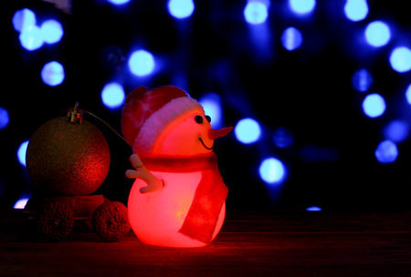 dcor: Dark evening red and blue Christmas and New Year`s card or poster with Snowman drags a truck ball on bokeh background. Place for product montage. Copyspace for sale price and item description. Stock Photo