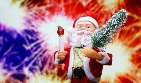 New Year`s card with Santa Claus toy brings Christmas tree at glow sparks bokeh background in the colors of the French flag. Copyspace concept for market banner, poster, congratulations.