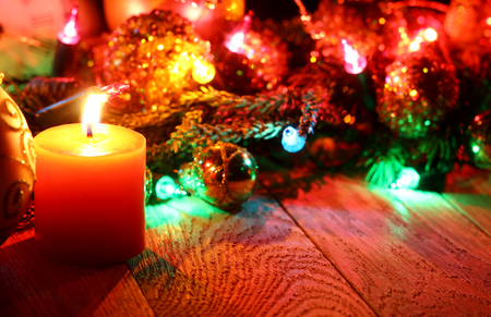 corner clock: New Year`s corner template  from Christmas tree fir branches, midnight clock, burning candle, golden pine cones, balls, garland lights on vertical old wooden desk table background. Big copyspace for holiday congratulations. Stock Photo