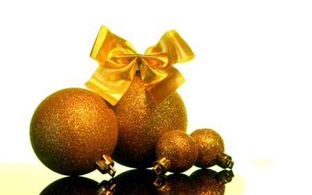 Christmas gold balls decorations with Bow of golden ribbons on a black mirror reflection surface and white background isolated