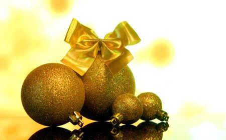 xmass: Christmas gold balls decorations with Bow of golden ribbons on a black mirror reflection surface and yellow bokeh background