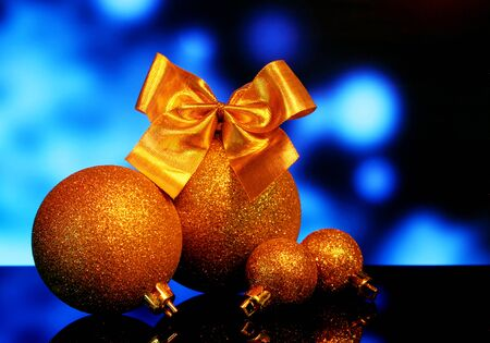 Christmas gold balls decorations with Bow of golden ribbons on a black mirror reflection surface and blue bokeh background Stock Photo