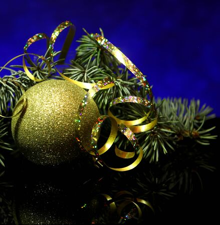 country style: Christmas gold decorations ball with fir tree brunch, golden ribbons on a black mirror reflection surface and blue bokeh background. New year`s vintage country style card. Stock Photo
