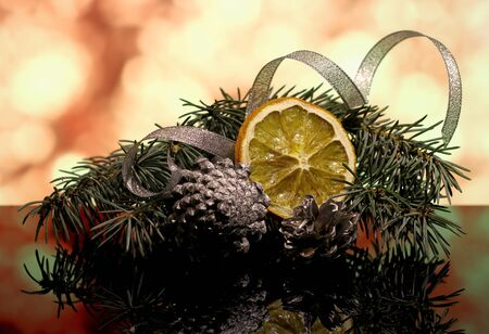country style: Christmas gold decorations with fir tree brunch, silver ribbons, dry oranges fruit and pine cones on a reflection surface and bokeh background with lights. New year`s vintage country style card. Stock Photo