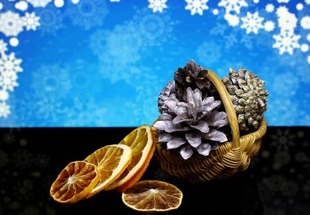 sky brunch: Christmas and New Year`s natural organic decorations with silver pine cones, dry orange fruits on a black reflection surface and blue snowy sky bokeh background with snowflakes.