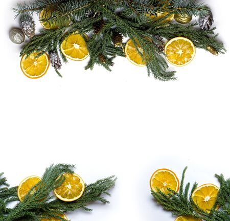 market bottom: Christmas top and bottom border frame of fir tree branch, golden pine cones, dry oranges fruit. New Year`s background for card, market winter sale banner or poster with copyspace for text. Isolated. Stock Photo