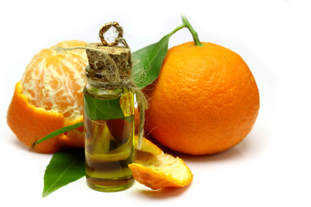perfume oil: Mandarin, tangerine citrus fruit, with green leaf, isolated on white background. Cosmetic Essence, perfume oil natural plant product in a glass bottle.  Pile of a fresh citrus.