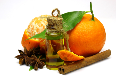 perfume oil: Mandarin, tangerine citrus fruit, with green leaf, isolated on white background. Cosmetic Essence, perfume oil natural plant product in a glass bottle. The aroma of cinnamon and star anise.