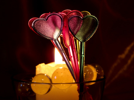 Love card with burning candle. Hearts on dark background. 14 February. Concept for Valentines day.