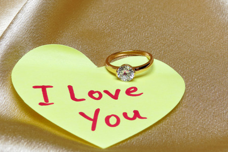 Marriage proposal card. Ring with diamond and inscription I love you on valentine heart from paper.